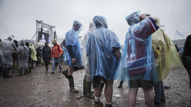 Festival goers standing and drinking in the rain at the Glastonbury Festival at Worthy Farm, Pilton on June 26, 2015
