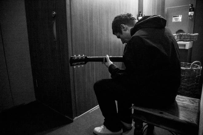 Liam Gallagher plays guitar backstage in the As It Was film documentary