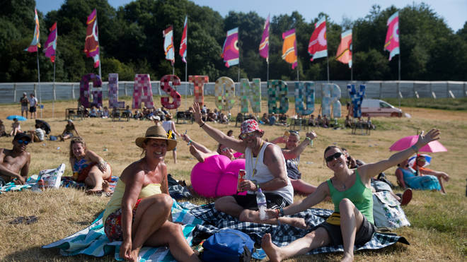 Glastonbury Festival goers behind the Glastonbury sign in 2017
