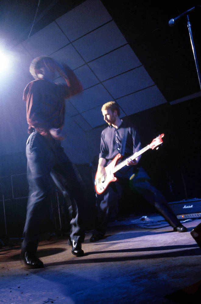 Ian Curtis and Peter Hook performing live onstage in London a few months after the release of Unknown Pleasures
