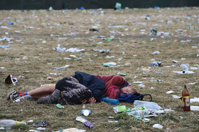 A couple sleep among the rubbish at the Pyramid Stage at Glastonbury 2019