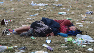 Couple sleep among the rubbish in front of The Pyramid Stage