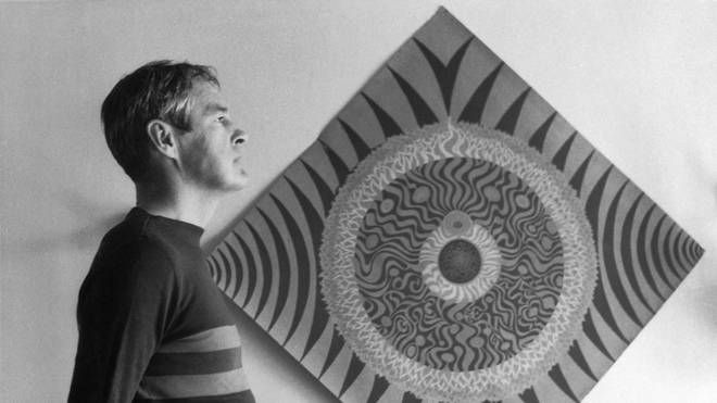 Psychologist and LSD proponent Timonthy Leary standing next to a mandala in 1966.