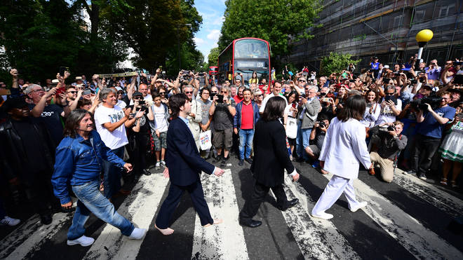 Beatles impersonators recreate the iconic 'Abbey Road' photograph made 50 years ago today, on August 8, 2019 in London