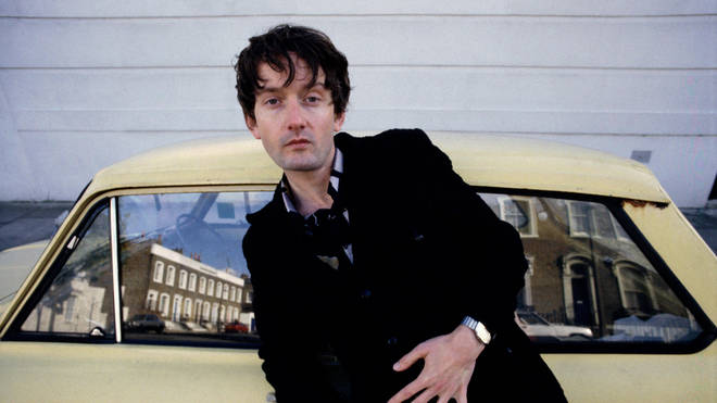 Pulp singer Jarvis Cocker, portrait, standing by a Hillman Imp car, London , United Kingdom, 1991.