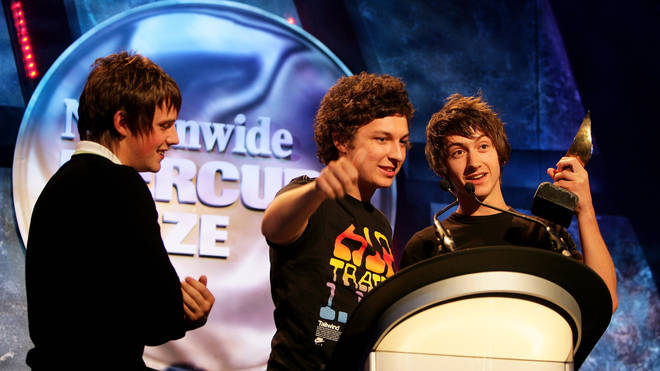 Jamie Cook, Matt Helders and Alex Turner accept the Nationwide Mercury Prize winners award