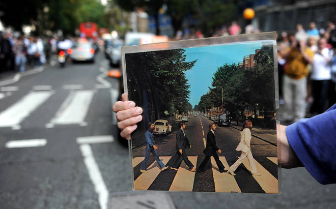 A Beatles fan holds his copy of Abbey Road up on the 40th anniversary of the crossing