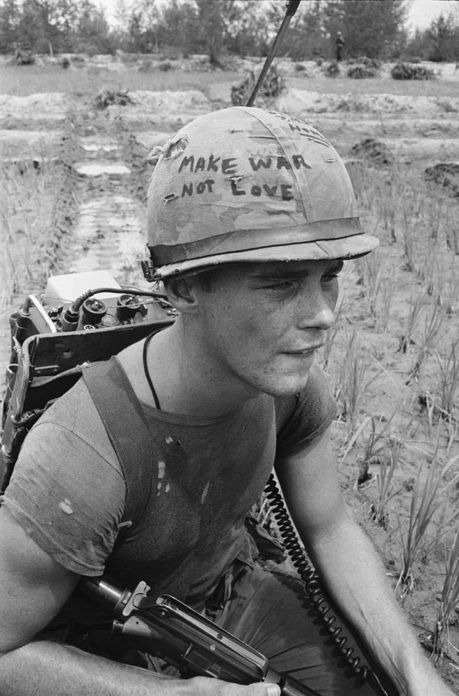 "Da Nang, South Vietnam: Marine Cpl. Michael Wynn, 20, of Columbus, Ohio, seems to be trying to get a message across with a takeoff of the hippie slogan ""make war not love"" written on his helmet here."
