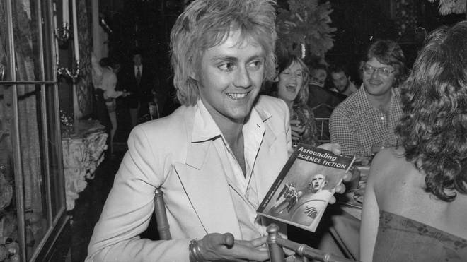 Roger Taylor receives a copy of Astounding Science Fiction during a party thrown for Queen by Elektra Records, 1977.