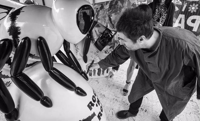 Liam Gallagher signs his Rock 'N' Roll Bee deisgned for Manchester's Bee in the City art trail