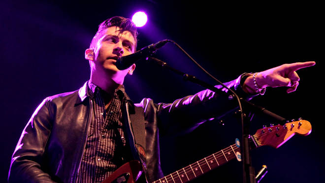 Alex Turner on stage with Arctic Monkeys in 2012