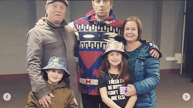 Liam Gallagher poses with 8-year-old superfan Luca and his family backstage at his Newcastle gig
