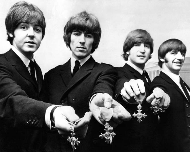 Paul McCartney, George Harrison, John Lennon and Ringo Starr proudly display their MBE medals after their investiture at the Palace. 1965